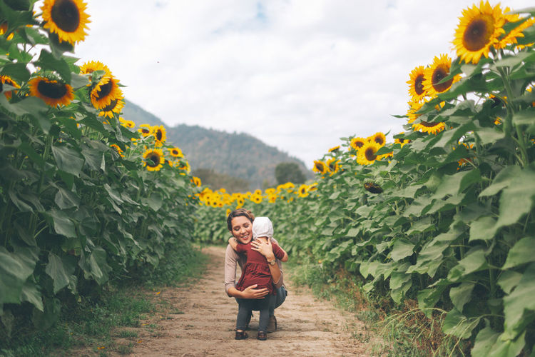A mother and her baby daughter in a sunflower field. Baby Daughters Family Field Love Mother Sunflower Adult Beauty In Nature Comforting Daughter Day Growth Holding Leisure Activity Lifestyles Nature One Person Outdoors Plant Real People Standing Human Connection