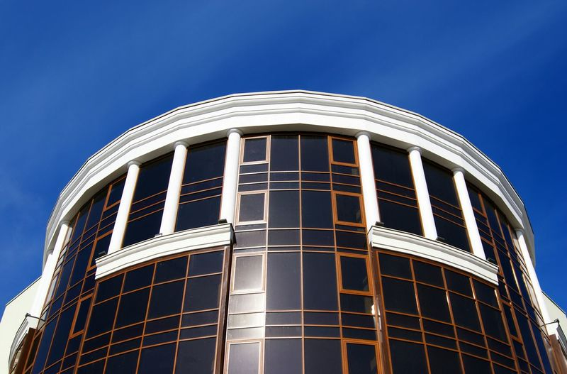 Low Angle View Of Office Building In City Against Blue Sky