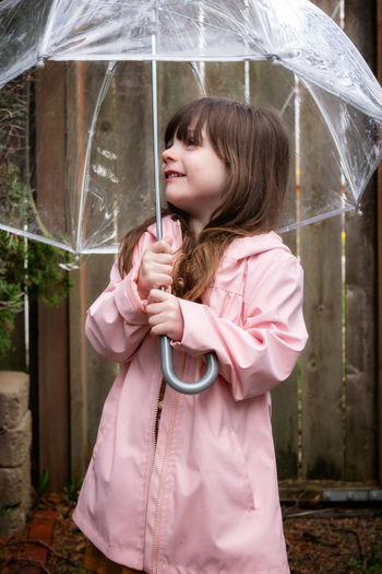 Cute girl holding umbrella while standing during rain