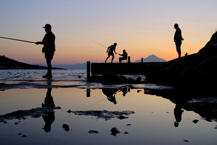 Silhouette people standing on shore against sky during sunset