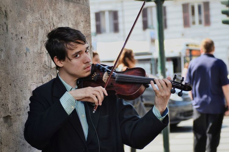 Portrait of street musician playing violin against wall