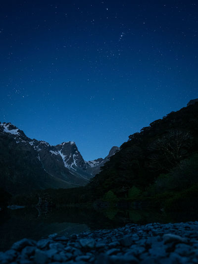 Scenic view of snowcapped mountains against starry sky at night