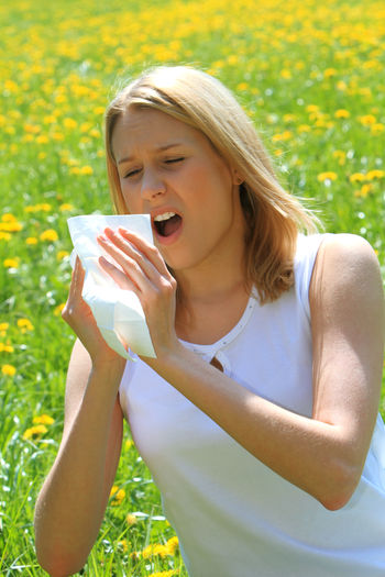 Young woman with a pollen allergy blowing in a handkerchief Flowering Plant Woman Blond Hair Day Ellergy Flower Flowers Girl Handkerchief Headache Illness Lifestyles Meadow Nature One Person Painful Pollen Pollen Allergy Sick Sickness Soft Tissue Spring Springtime Young Adult Young Women