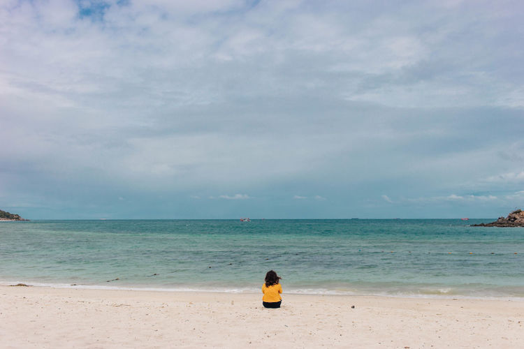 Woman wearing yellow shirts sitting at the beach Beach Beauty In Nature Day Horizon Over Water Leisure Activity Lifestyles Nature One Person Outdoors People Real People Rear View Sand Scenics Sea Shore Sky Standing Tranquility Vacations Water Wave
