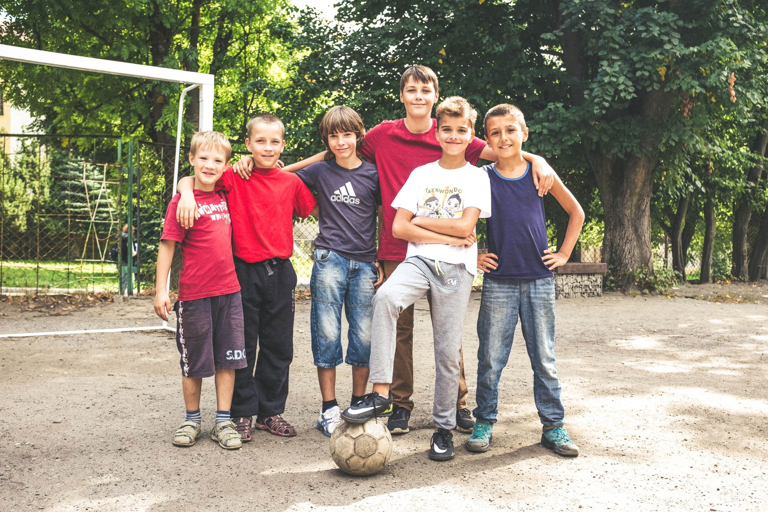 full length, looking at camera, portrait, front view, friendship, togetherness, boys, standing, child, childhood, casual clothing, day, smiling, outdoors, group of people, people, bonding, cheerful, teamwork, children only, tree, adult, sports team