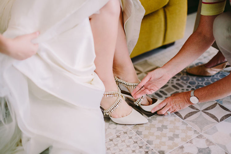 Cropped woman putting shoes on feet of bride