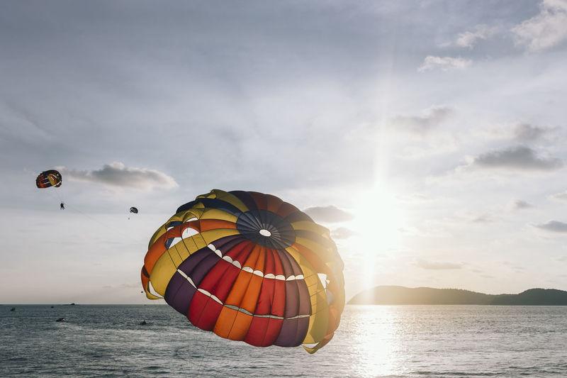 Parachutes at sea against sky
