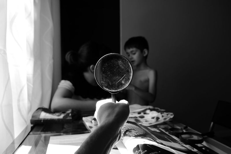 Cropped Image Of Hand Holding Magnifying Glass Against Mother And Son At Home
