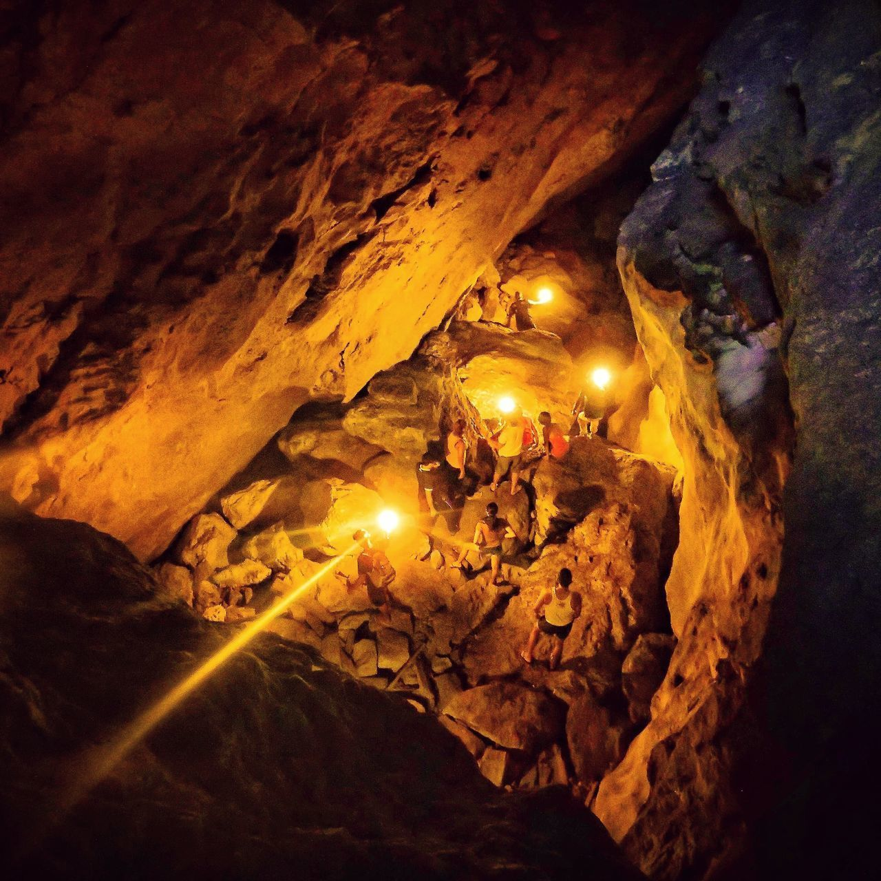 rock formation, rock - object, cave, illuminated, real people, nature, leisure activity, adventure, beauty in nature, indoors, physical geography, scenics, one person, night, water, sky, people