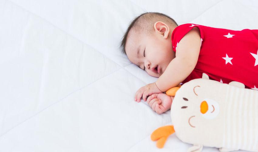 High angle view of baby girl sleeping on bed