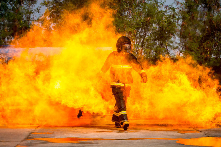 Full Length Of Firefighter Walking Amidst Fire