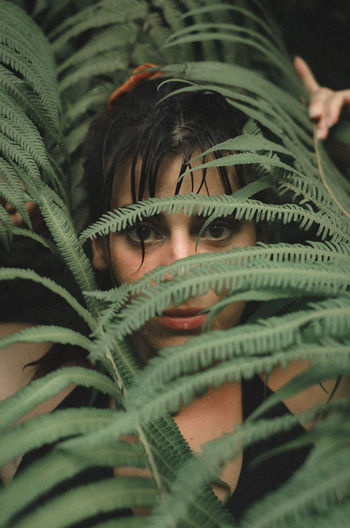 Close-up portrait of woman standing by plants