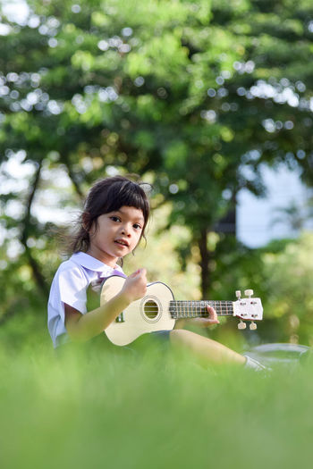 Portrait of girl playing ukulele while sitting on field at park