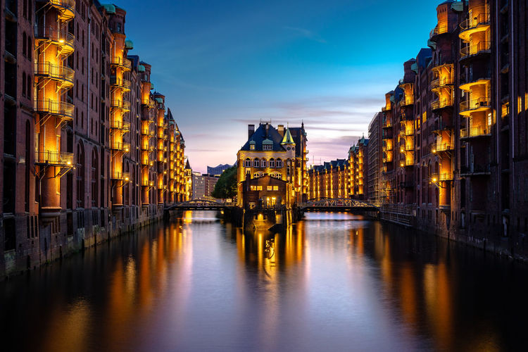 Illuminated buildings by river at sunset