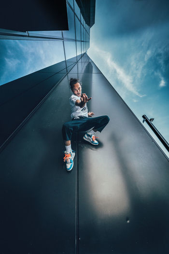 Young man sitting on wall against sky