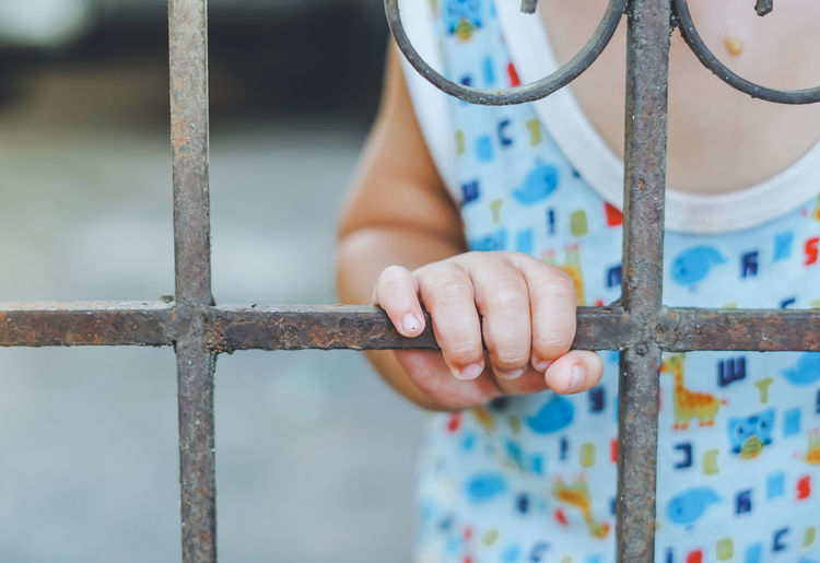 Close up, Baby's hand holding a steel metal cage. Baby Crime Hand Holding Locked Security Baby Boy Behind Boy Cage Caged Freedom Close-up Day Finger Hand Human Body Part Human Hand Illegal Legal Lock Metal Cages One Person Outdoors Real People Steel Structure  Violence