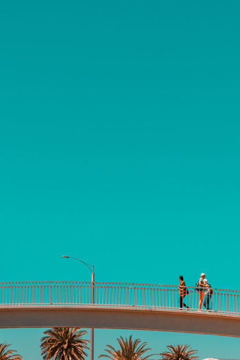 People walking against clear blue sky