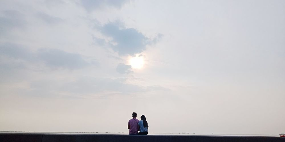 Couple Sitting Against Sky During Sunset