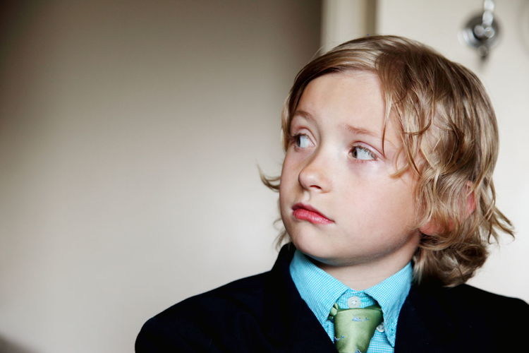 Close-up of boy wearing suit looking away and standing at home