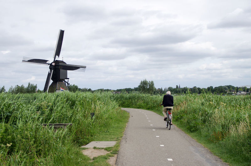 Man cycling with a windmill in the background Windmill Bicycle Cloud - Sky Day Diminishing Perspective Field Landscape Lifestyles Mode Of Transportation Nature One Person Outdoors Real People Rear View Riding Road Sky Transportation