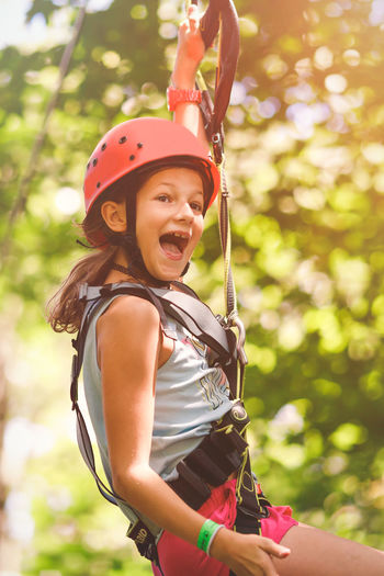 Young girl going by flying fox in forest rope climbing park Climbing Climbing Park Day Family Activity Forest Rope Park Helmet Leisure Activity Lifestyles Nature One Person Outdoors Protection Real People Rope Safety Safety Harness Summer Holiday Sunny Day Teambuilding Tree Summer Sports