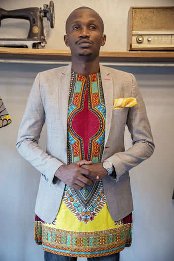 Fashion Designer African Fabric Wristwatch Blazer - Jacket Traditional Clothing Male Model Black Model Front View One Person Standing Real People Lifestyles Indoors  Leisure Activity Young Men Men Young Adult Three Quarter Length Clothing Waist Up Looking At Camera Casual Clothing Adult Portrait