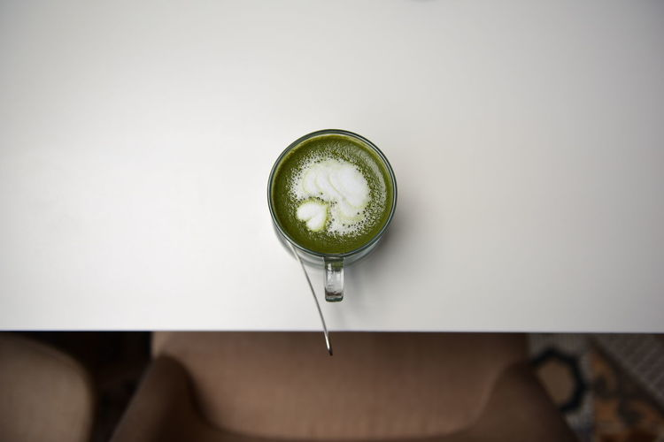 Directly above shot of matcha tea served on white table