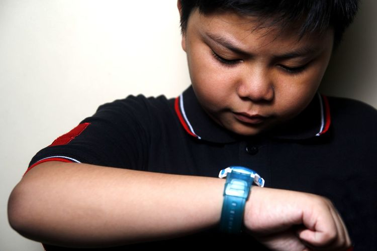 Close-Up Of Overweight Boy Checking Time Against Wall