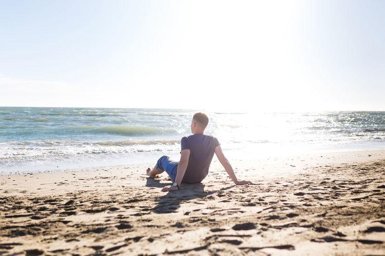 Full length of man sitting on shore at beach against sky