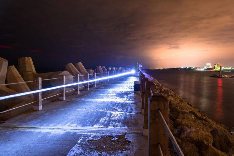 Light trail on footpath amidst sea at night