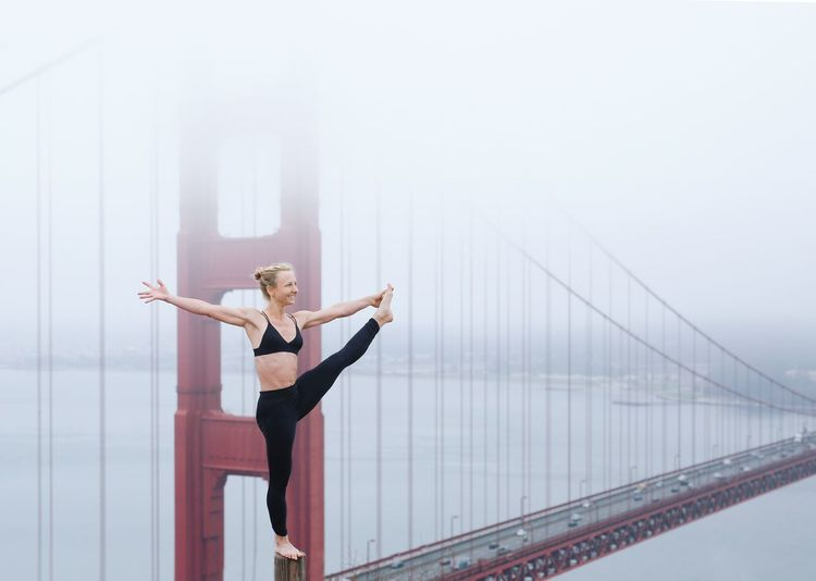 Woman doing yoga against golden gate bridge