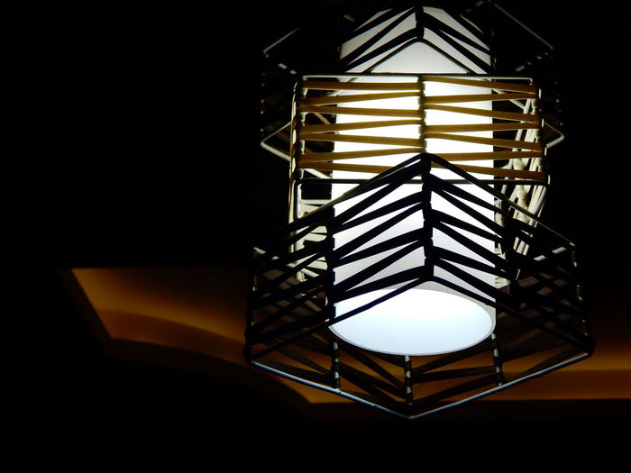 Low angle view of illuminated lamp in darkroom