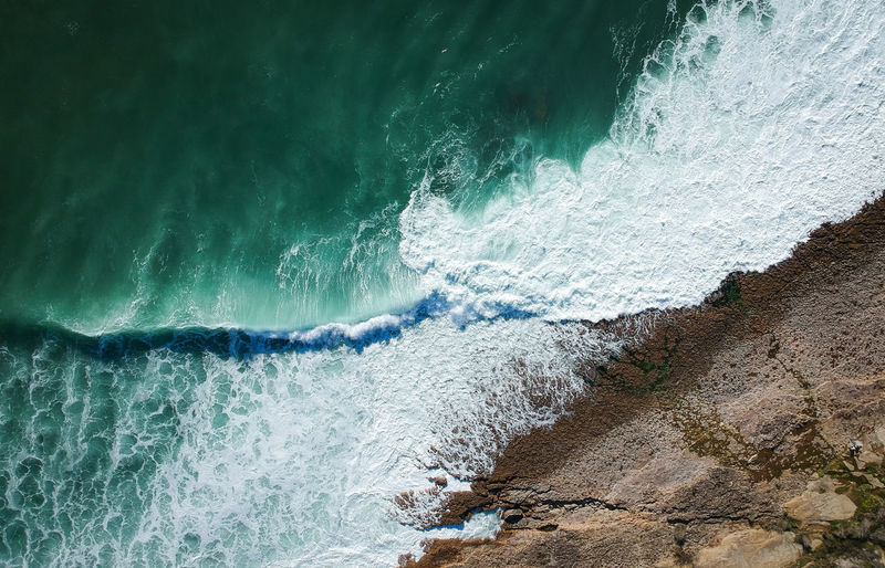 Aerial view of waves splashing on rocks