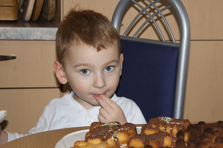 Portrait of cute boy eating cookies on table at home