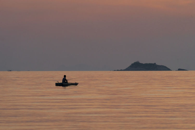 Man on boat at sea against sky during sunset