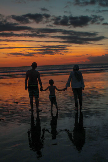 Family Standing On Shore At Beach Against Orange Sky During Sunset