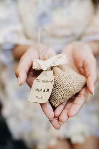 Midsection of hand holding small jute sack with text