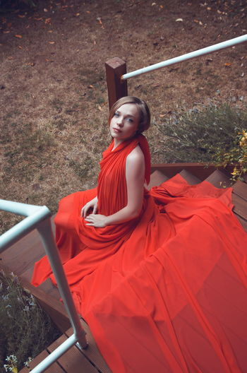 High Angle Portrait Of Beautiful Woman Wearing Red Dress While Sitting On Steps