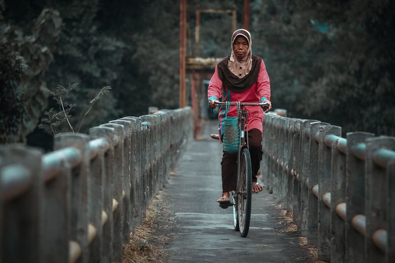Portrait of woman riding bicycle on the small bridge
