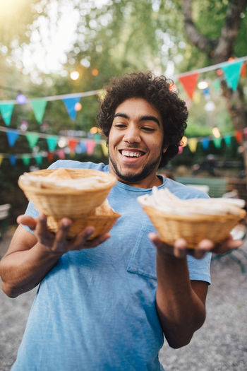 Smiling young man carrying food in bowls during garden party