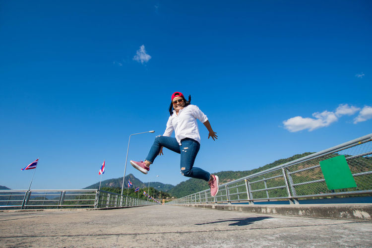 Low Angle View Of Woman Jumping On Jetty Against Blue Sky