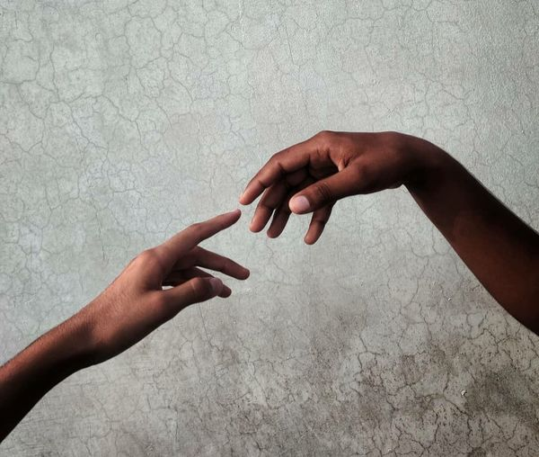 Close-up of hand holding hands against wall