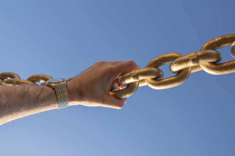 Large chain with sky background hand holding on. Chain Chainlink Blockchain Technology Industry Banking Concept Finance Future Commerce Ecommerce Sky Blue Connected Network Security Bitcoin Ethereum Peer To Peer Ledger Business Solid Gold Copy Space Cryptocurrency