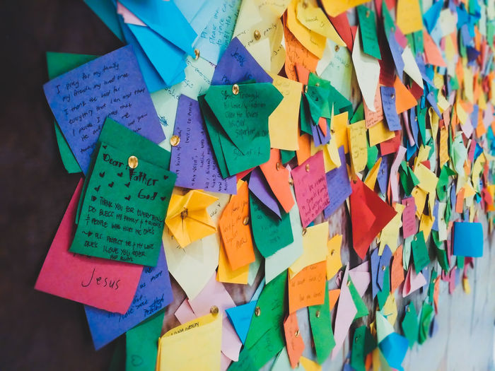 Close-up of prayer messages papers attached on board at church