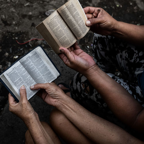 Bible comparing in the slum Bible Studying Slum Study Faith Believe Faithful Religion Religious  Christian New Testament Human Hand Dumpsite Poverty Hope Belief Book Bibel  Glaube Philippines Reading Compare