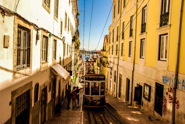 Tramway Amidst Buildings On Street Against Sky In City