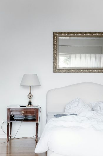 Table lamp by cropped bed in the bedroom