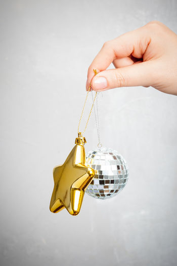 Mirror ball and christmas star Close-up Day Gold Colored Grey Background Holding Human Body Part Human Hand
