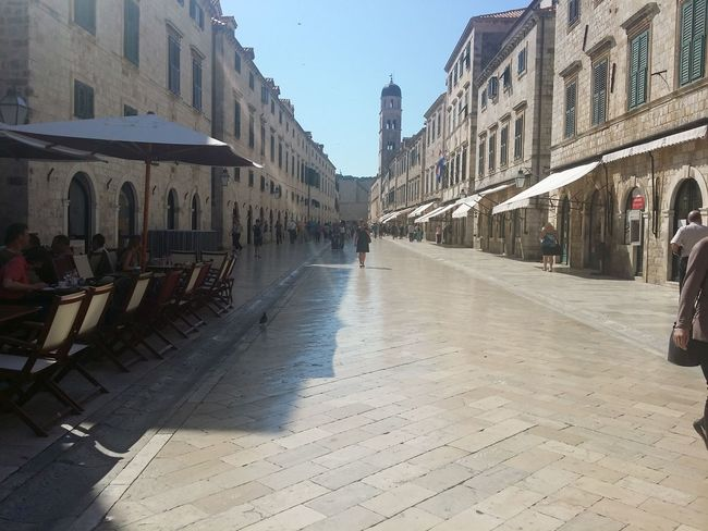 Architecture Building Exterior Built Structure City City Life Clear Sky Cobblestone Day Diminishing Perspective Incidental People Large Group Of People Lifestyles Men Person Street The Way Forward Transportation Vanishing Point Walking