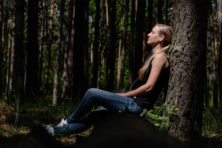 A girl in a forest sits leaning against a tree, headphones listening to music. positive emotion.